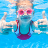 Girl underwater with thumbs up